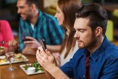 Homme avec le smartphone et les amis au restaurant Photographie stock