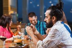 Homme avec le smartphone et les amis au restaurant Photo libre de droits