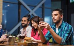 Homme avec le smartphone et les amis au restaurant Photos libres de droits