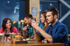 Homme avec le smartphone et les amis au restaurant Photo stock