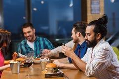 Homme avec le smartphone et les amis au restaurant Images stock