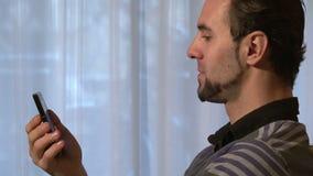Homme avec le smartphone occupé dans un appel visuel banque de vidéos