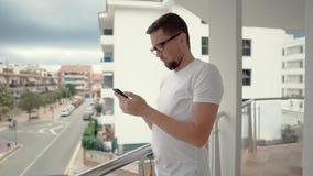 Homme avec le smartphone sur le balcon banque de vidéos