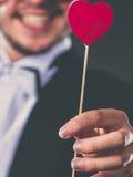 Homme avec le symbole d'amour de bâton de coeur à disposition Photographie stock libre de droits