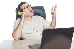 Homme avec le téléphone à disposition se reposant à un ordinateur portable Images libres de droits