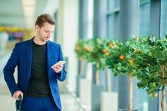 Homme avec le téléphone intelligent à l'intérieur dans l'aéroport Veste de port de costume de jeune garçon occasionnel Homme cauc Image libre de droits