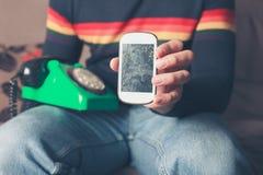 Homme avec le téléphone intelligent cassé et le téléphone rotatoire Photographie stock