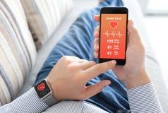 Homme avec le téléphone intelligent de participation de montre avec la santé sur l'écran photographie stock