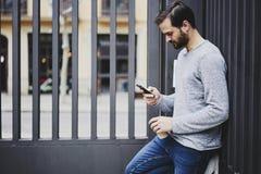 Homme avec le téléphone portable à accrocher ensemble le week-end la position sur le fond urbain Photos stock