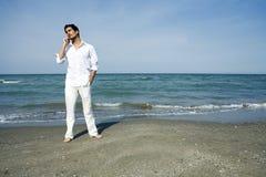 Homme avec le téléphone portable à la plage Photos stock