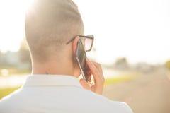 Homme avec le téléphone portable dans des mains, vue arrière, extérieure Photos libres de droits