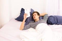 Homme avec le téléphone portable dans le lit Images libres de droits