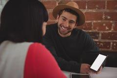 Homme avec le téléphone portable regardant l'amie en café Photos libres de droits