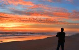 Homme avec le téléphone sur la plage au lever de soleil Photos stock
