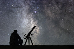 Homme avec le télescope d'astronomie regardant les étoiles photographie stock libre de droits