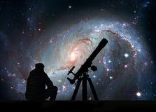Homme avec le télescope regardant les étoiles Crèche stellaire NGC 167 images stock