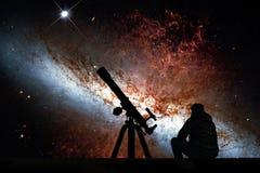 Homme avec le télescope regardant les étoiles 82 plus malpropres Image stock