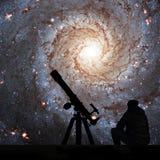 Homme avec le télescope regardant les étoiles 74 plus malpropres, NGC 628 Photo libre de droits