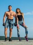 Homme avec le torse musculaire dans les shorts de denim et la fille blonde utilisant les jeans supérieurs et déchirés noirs s'exe Photo stock