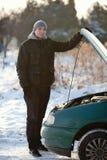 Homme avec le véhicule cassé en hiver Images stock