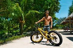 Homme avec le vélo de sport détendant sur la plage tropicale en été Image stock
