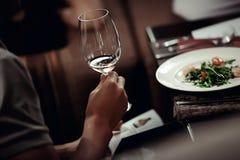 Homme avec le verre de vin dans un main et menu Photographie stock libre de droits