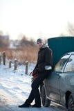 Homme avec le véhicule cassé en hiver Photographie stock