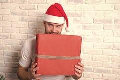 Homme avec le visage adroit dans la boîte rouge de prise de chapeau de Santa photo stock