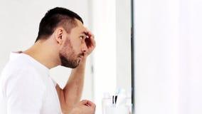 Homme avec le visage de nettoyage de lotion ou de toner à la salle de bains banque de vidéos