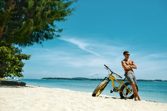 Homme avec le vélo de sable sur la plage appréciant des vacances de voyage d'été Photo libre de droits