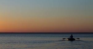 Homme avec les avirons sur l'eau en mer Image stock