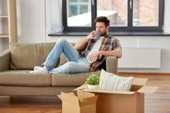 Homme avec les boîtes et le café potable à la nouvelle maison photographie stock