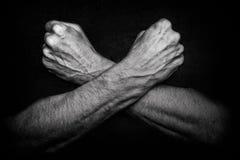 Homme avec les bras croisés sur l'obscurité Image stock