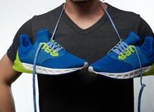 Homme avec les chaussures accrochantes sur le cou Photo stock