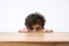 Homme avec les cheveux bouclés jetant un coup d'oeil par derrière le bureau photos stock