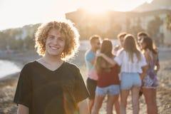 Homme avec les cheveux bouclés se tenant sur la plage avec son sourire d'amis Image stock