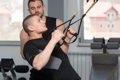 Homme avec les courroies personnelles de Train Trx Fitness d'entraîneur images stock