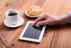 Homme avec les croissants numériques et le café de comprimé Image libre de droits