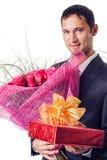 Homme avec les fleurs et le cadeau Photographie stock libre de droits