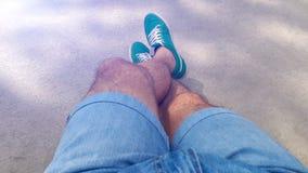 Homme avec les jambes velues dans des shorts de denim et des espadrilles vertes Image libre de droits
