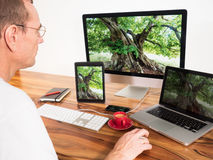 Homme avec les ordinateurs et les périphériques mobiles reliés au réseau Image libre de droits