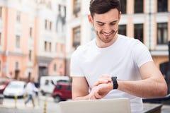 Homme avec plaisir agréable à l'aide de la montre intelligente Photos libres de droits