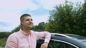 Homme avec plaisir gai se penchant sur sa voiture dehors clips vidéos