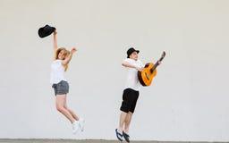 Homme avec sauter de guitare et de femme images libres de droits