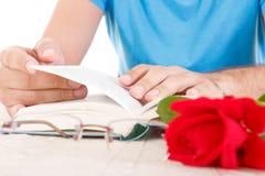 Homme avec ses mains tenant le livre ouvert et poussant des feuilles par des pages Image libre de droits