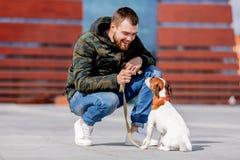 Homme avec son chien, Jack Russell Terrier, sur la rue de ville photo stock