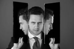 Homme avec trois visages dans des deux miroirs images libres de droits