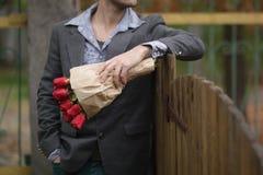 Homme avec un bouquet des roses Images stock