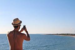Homme avec un chapeau de paille faisant une photo Photographie stock libre de droits