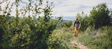 Homme avec un chien marchant le long d'un sentier de randonnée Image libre de droits